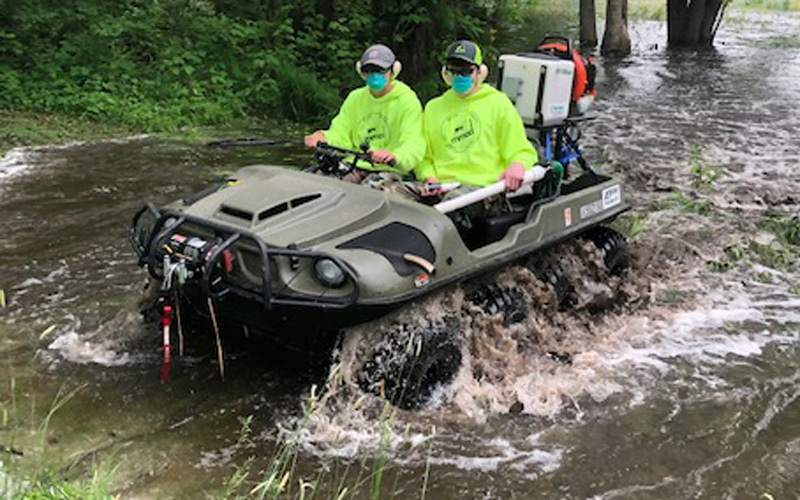 Staff driving through flooded waters in ATV.